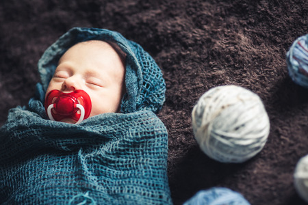 Newborn baby sleeps wrapped in blanket amidst tangles of thread.