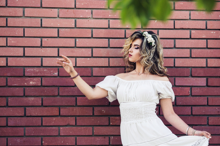 Beautiful girl in white dress is standing near brick wall and posing. Frame made of green leaves Stock Photo