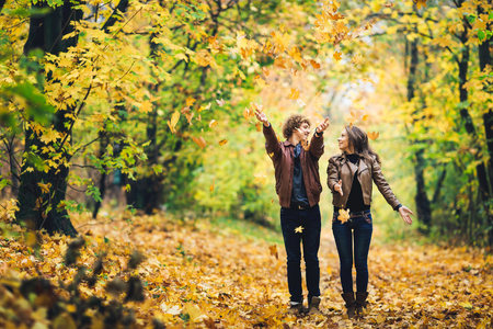 loving couple in an autumn park. Man and woman cheerfully throw yellow leaves up Фото со стока