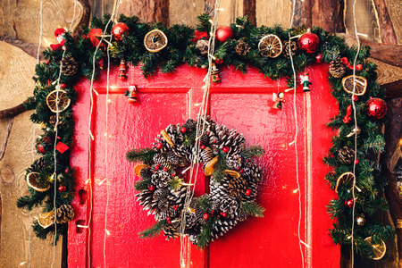 Fragment of red wooden door with Christmas decoration Stock Photo