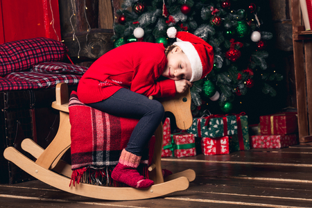 Santa girl riding rocking horse on background of Christmas decorations