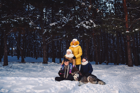Happy european young family with big dog posing against winter pine forest. The concept of a winter holiday. Horizontal photo of a family in full growth.