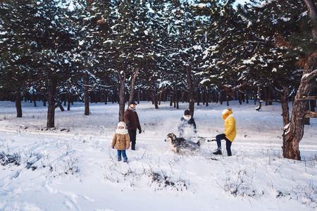 Happy young caucasian family plays with a dog in winter in a pine forest. Photo for advertising family winter outdoor activities. Horizontal photo of a family in full growth.
