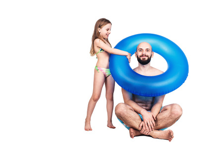 Happy bearded father and little girl with inflatable circle isolated on white background. summer holiday concept