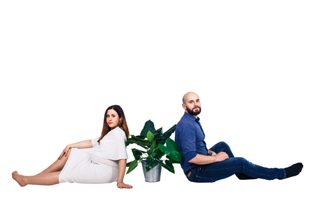 The couple is sitting on the floor. A green houseplant in a bucket stands between a pregnant girl and a bearded guy. family day. Isolated on white Foto de archivo