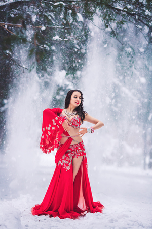 beautiful young girl dancing belly dance in red dress in winter in a park on the snow