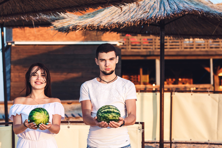 boy and girl stand on the beach and hold watermelons