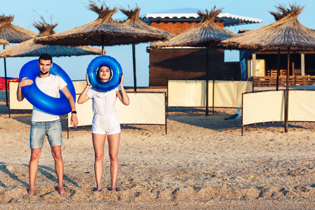 man and woman are posing on the beach and holding inflatable circles. concept of summer sea holiday