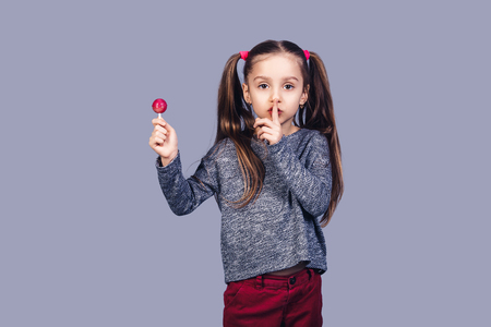 little cute girl holds red lollipop in hand and shows shh. isolated on gray background Stock fotó