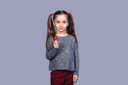 little cute girl holding a red lollipop. isolated on gray background