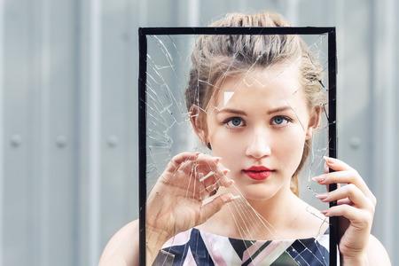 Beautiful teen girl holding broken glass in her hands. concept feminism Archivio Fotografico
