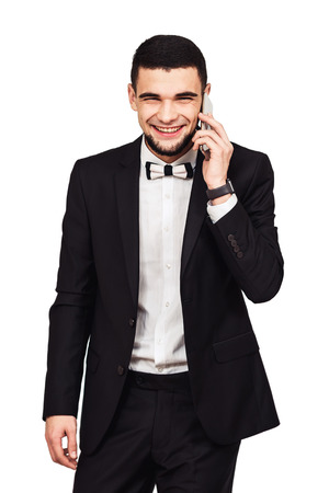 cheerful bearded man in a black suit speaks by phone. isolated on white Foto de archivo