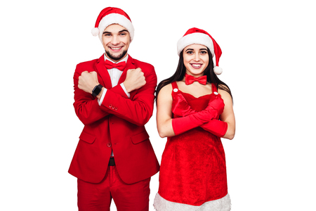 young couple having fun at a christmas theme party. young man and woman in red suits with Santa hats. isolated on white