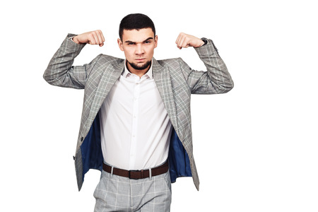 self-confident businessman. Stylish young bearded guy in a gray suit shows his biceps. isolated on white