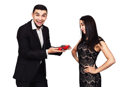 the young bearded man gave his girlfriend toy car, the girl is not happy with such gift. isolated on white
