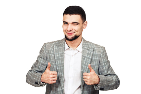 I like it. stylish young bearded guy in a gray suit posing on a white background.