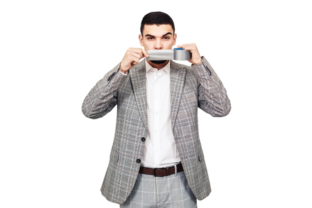 fighter for freedom of speech. Stylish young bearded guy in a gray suit wants to cover his mouth with adhesive tape. isolated on white