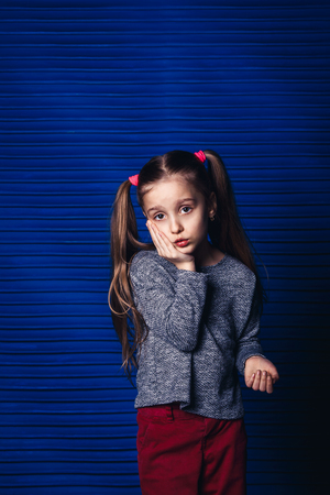 sad little girl holding her cheek on a blue background. child toothache concept 版權商用圖片