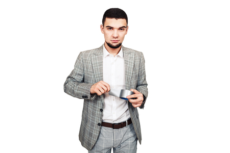 opponent of free speech, dictator. Stylish young bearded guy in a gray suit wants to seal your mouth with adhesive tape. isolated on white Stockfoto
