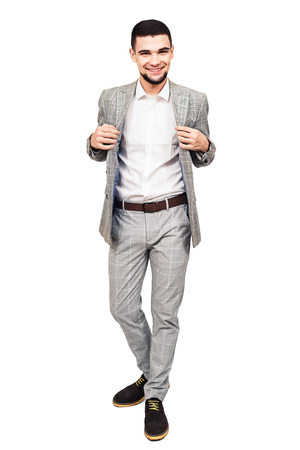 stylish young bearded guy in a gray suit posing on a white background.