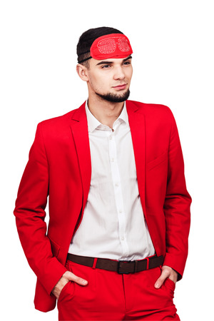 young businessman relies on luck, fortune. bearded man in a red suit with a red blindfold. isolated on white 스톡 콘텐츠