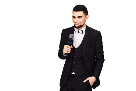 stylish elegant cheerful man in a black suit with a microphone in his hand crosses his eyes. isolated on white Stock Photo