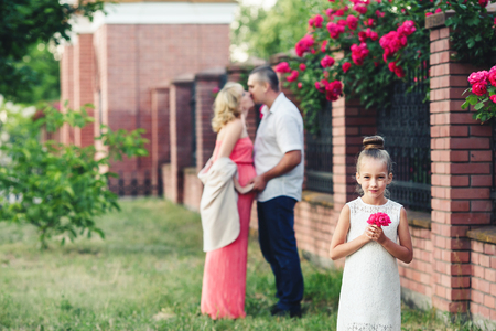Family in nature near the fence with blooming roses.