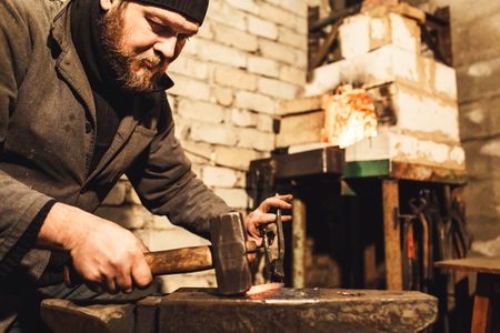 Blacksmith forges a hot metal on the anvil with a hammer