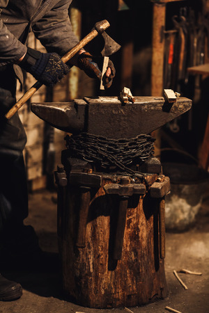 blacksmith splits firewood for kindling the furnace