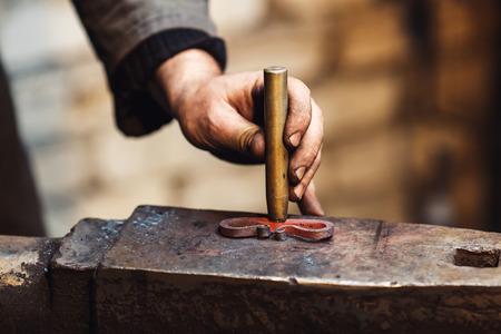 close-up blacksmith stigmatizes his product Stock Photo