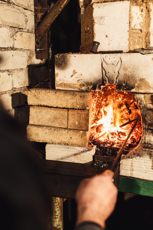 a blacksmith kindles a fire in the furnace