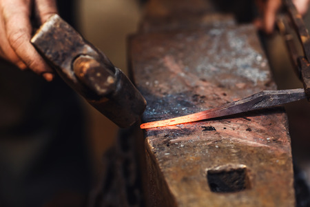blacksmith makes an artistic forging of hot metal on the anvil