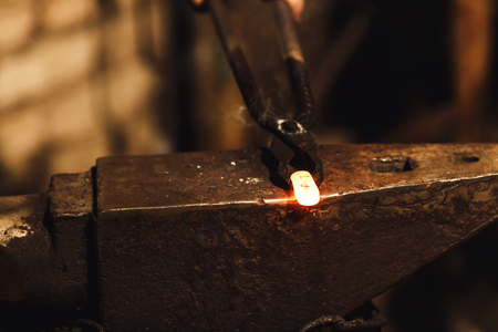 The blacksmith manually forging the red-hot metal on the anvil in smithy Imagens