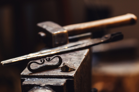closeup of a blacksmith anvil with a hammer, tongs, firesteel and flint