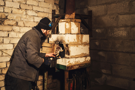 bearded blacksmith kindles a fire in the furnace