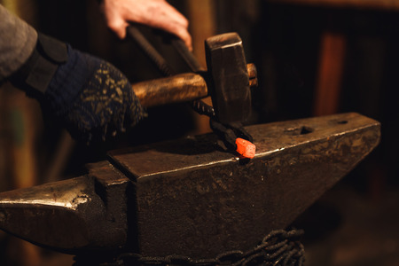 The blacksmith manually forging the red-hot metal on the anvil in smithy Stock Photo