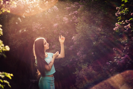 Wonderful spring. A beautiful young girl enjoys nature and sunlight among the blossoming lilac
