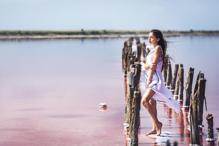 beautiful young girl in long white dress posing on salty pink lake