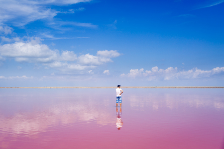 man stands in middle of a salty pink lake