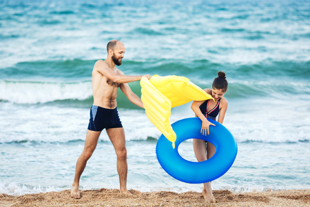 father and daughter play on sea beach and fight comically