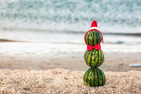 summer snowman from watermelons in a red bow-tie and Santa's hat Stock Photo