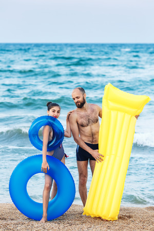joyful father and daughter are standing on beach holding an inflatable mattress and circle