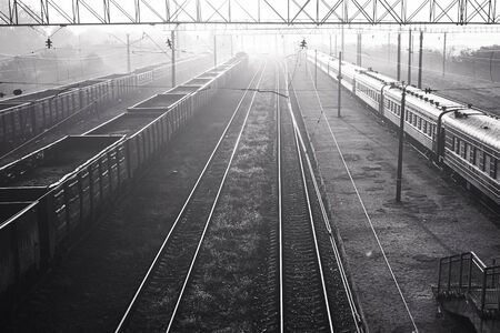 black and white photo of railway tracks in fog with passenger and freight trains