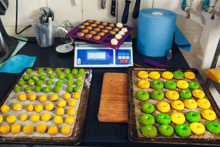Confectioners workplace. Yellow and green profiteroles on a baking sheet.