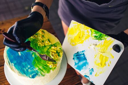 confectioner decorate cake with colorful cream. handmade cake with pattern