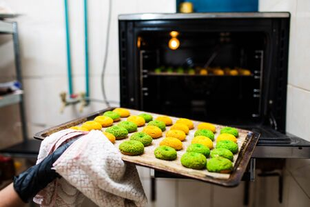 confectioner takes out a baking sheet with round green and yellow eclairs from the oven.