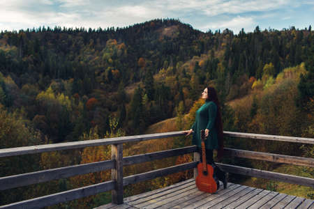 Long-haired girl holds guitar, standing near parapet in mountains in autumn Archivio Fotografico