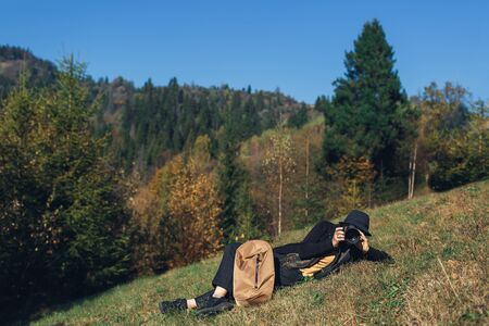 girl photographer with backpack lies on slope and shoot wildlife in mountains in autumn