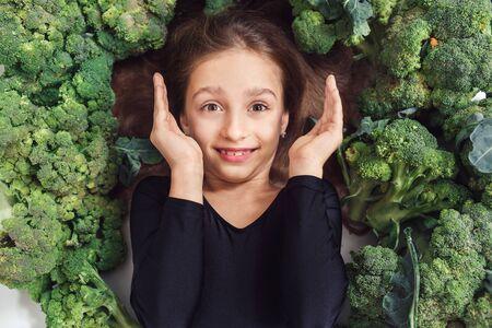 cheerful child girl lies among broccoli and laughs. nutrition and healthy eating habits for kids concept. hair and skin health.