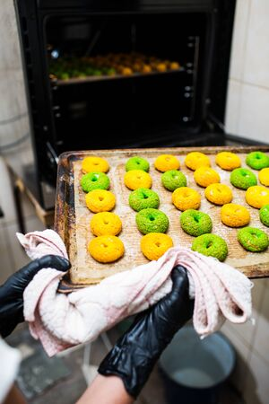confectioner takes out a baking sheet with round green and yellow eclairs from the oven. Crispy Craquelure Profiteroles